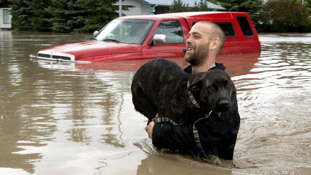 A man carries his dog in flood waters in Canada