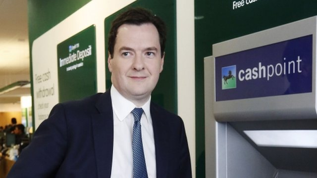 Chancellor George Osborne standing by a cash machine
