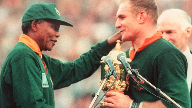 Springbok Captain Francois Pienaar (R) receives the Rugby World Cup from President Nelson Mandela at Ellis Park in Johannesburg on 24 June 1995.