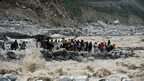 Stranded Indian pilgrims wait to be rescued on the side of a river at Govind Ghat on 23 June 2013
