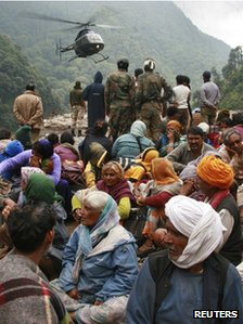 Stranded people wait for their turn to be rescued by a helicopter in Uttarakhand on 23 June 2013