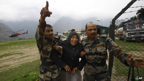 An injured pilgrim cries as army soldiers carry her after she was rescued in Uttarakhand on 24 June 2013