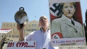 A Greek protester holds a poster of Angela Merkel