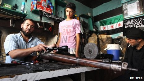 Abu Mohammad, a gunsmith, repairs a gun in his shop in the city of Aleppo