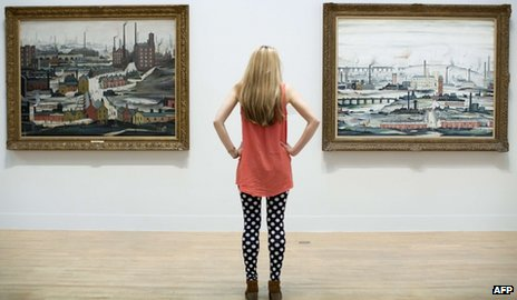 "An employee poses for a picture in front of English artist Laurence Stephen Lowry""s paintings ""Industrial Landscape (Ashton Under Lyne 1952) (L) and ""Industrial Landscape 1955"" (R) at the Lowry and the Painting of Modern Life exhibition at Tate Britain in London on June 24, 2013."