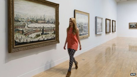 "A museum employee walks past English artist Laurence Stephen Lowry""s painting ""The Pond 1950"" at the Lowry and the Painting of Modern Life exhibition at Tate Britain in London on June 24, 2013"
