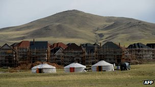 New housing under construction is pictured behind traditional Mongolian tents called a ger or yurt outside Ulan Bator, 4 June 2013