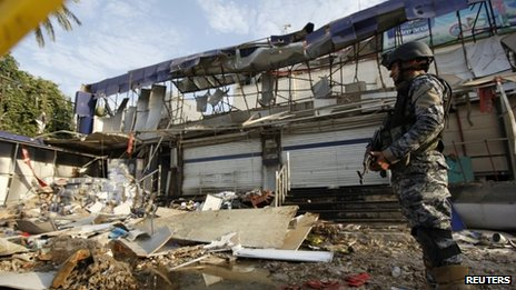 An Iraqi policeman stands guard at the site of a car bomb attack in Baghdad