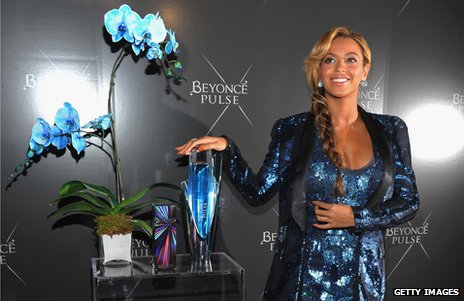 Beyonce standing next to a bottle of perfume she is endorsing