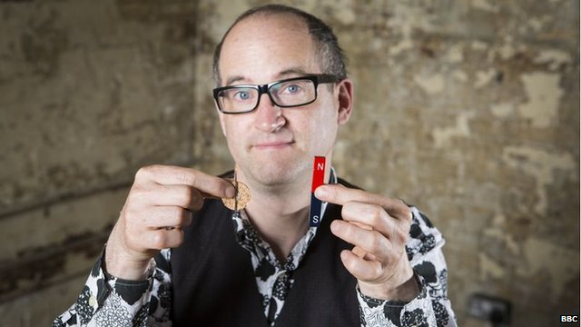 Mark Miodownik holds a magnet and a needle