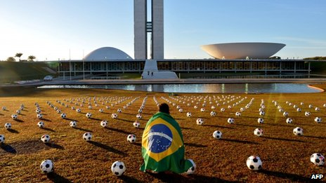 A man with a Brazilian flag crouches among the footballs placed in front of the National Congress building in Brasilia on 26 June 2013