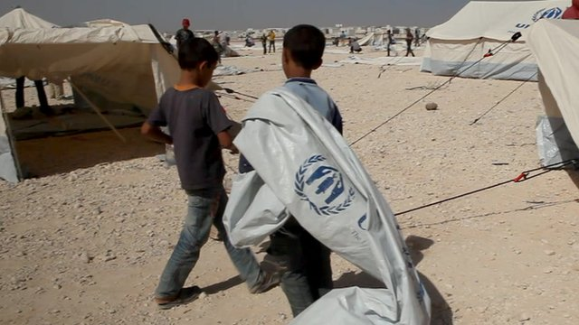 Two young boys carrying a tent in a refugee camp