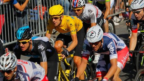Multi-branded cyclists compete in the 2012 Tour De France