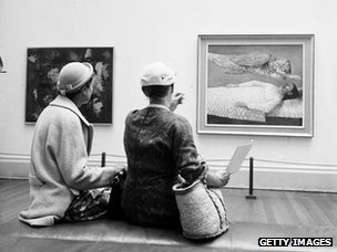 Visitors evaluate a painting at an exhibition of modern art, organised by the Contemporary Art Society on the theme of religion, in London's Tate Gallery