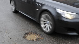 Car passes pothole