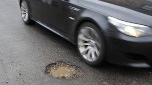 Car passes pothole