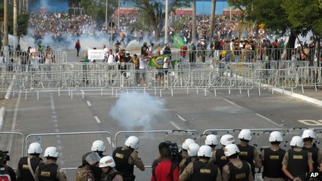 Police fire tear gas at protesters trying to reach the Mineirao Stadium where Brazil was playing Uruguay