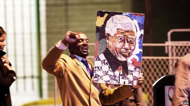 A man holds a picture of Mandela outside the hospital.