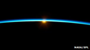 The Sun rises, illuminating the Earth's atmosphere