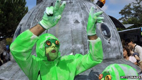 A man in a green costume in front of a UFO