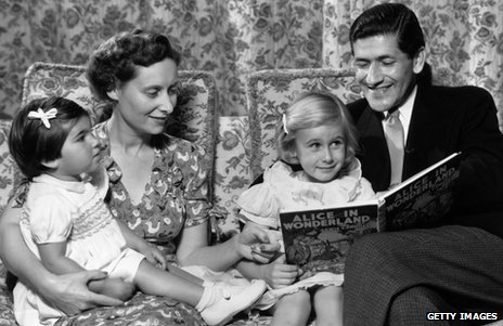 An old photo of parents reading Alice in Wonderland to their children