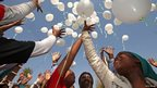 Children raise toward the sky after releasing the white balloons outside the hospital in Pretoria (27 June 2013)