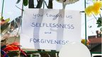 "A handwritten poster against railings outside the hospital reads: ""You taught us selflessness and forgiveness"""