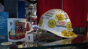A miner's helmet covered in stickers