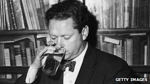 Dylan Thomas drinking a glass of beer and smoking while seated at a desk with stacks of his books of poetry, New York City, c. 1950