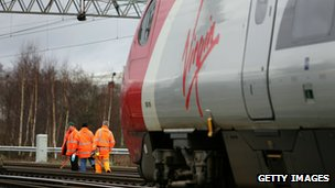 As a Virgin pendolino train passes workers from Network Rail check points and track at Crewe Grand Junction on the West Coast mainline