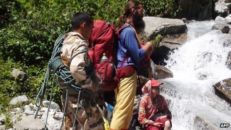 Indian security personnel help rescue foreign visitors stranded by flood waters in Uttarakhand state, on June 22, 2013