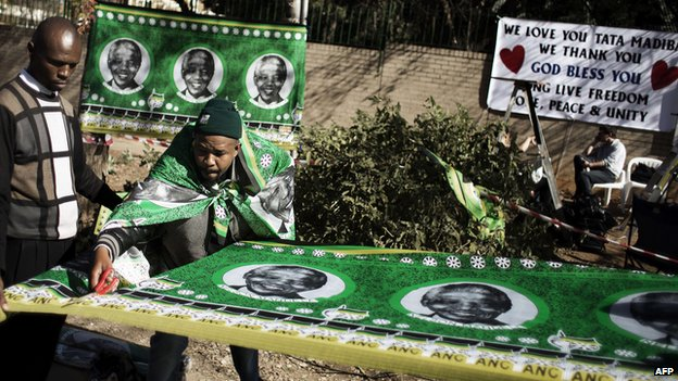 Vendor cuts fabric with portraits of Nelson Mandela outside the hospital in Pretoria on 28 June 2013