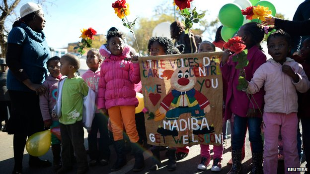 Children hold a banner outside the hospital in Pretoria on 28 June 2013