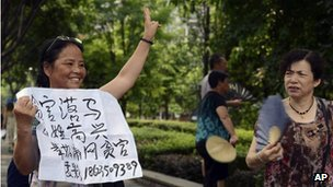 A woman holds up an anti-corruption sign  outside the court where Lei Zhengfu was tried (19 June 2013)