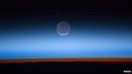 Noctilucent clouds from space station with moon in background