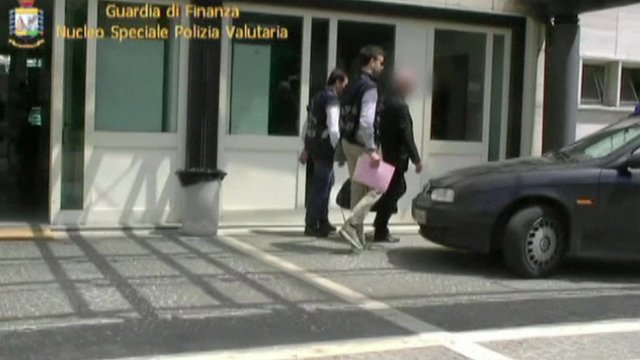 Nunzio Scarano leaving building accompanied by policemen