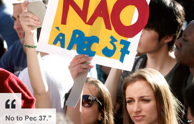 Sao Paulo protester holds banner against  PEC 37 -  a constitutional amendment which would limit the power of federal prosecutors to investigate crimes 22 June