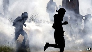 Protesters run from tear gas fired by police in Fortaleza. Photo: 27 June 2013