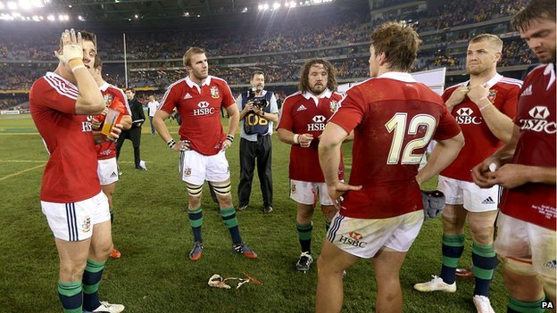 Lions players stand on rugby pitch after losing the second test to Australia