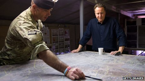 David Cameron being shown a map by a soldier