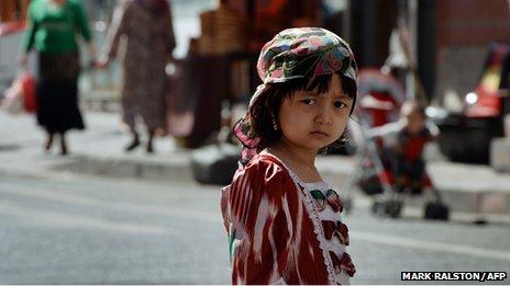 A young Uighur girl waits near the main bazaar in the Muslim quarter of Urumqi, Xinjiang Province on June 29, 2013