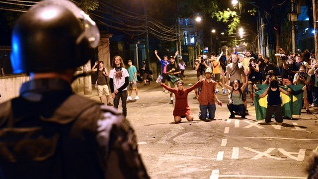 A riot squad officer in Rio de Janeiro faces protestors