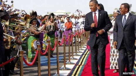 US President Barack Obama dances as a Tanzanian band plays during an official arrival ceremony at Julius Nyerere Airport in Dar es Salaam, Tanzania, 1 July 2013; at right is Tanzanian President Jakaya Kikwete