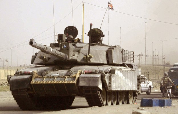 A British Challenger 2 tank driving down a road into Basra, Iraq, in 2006