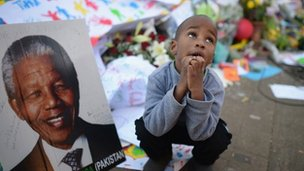 People gather for Nelson Mandela outside the Mediclinic Heart Hospital where he is being treated for a lung infection on June 30, 2013 in Pretoria, South Africa.
