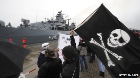 Relatives wave a pirate flag as a frigate returns from anti-piracy mission Somalia in 2009