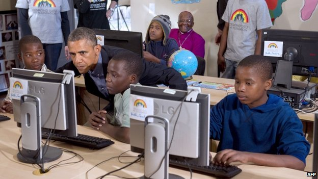 US President Barack Obama (2L) sits down at a computer as he tours a classroom at the Desmond Tutu HIV Foundation Youth Centre in Cape Town, South Africa, on 30 June 2013