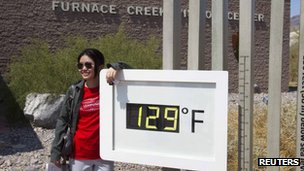 Jing Jing, a student from China, poses in front of an unofficial temperature gauge at the Furnace Creek Visitor Center in Death Valley National Park in California 29 June 2013