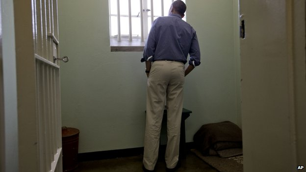 US President Back Obama peers out from Section B, prison cell No 5, on Robben Island, South Africa, Sunday, 30 June  2013