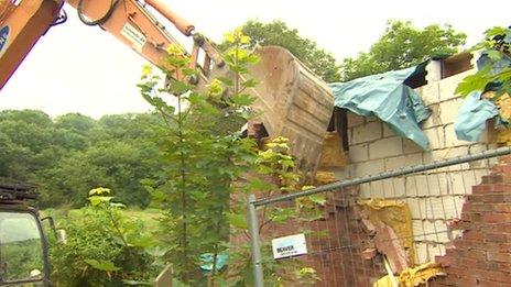 Digger demolishing the house